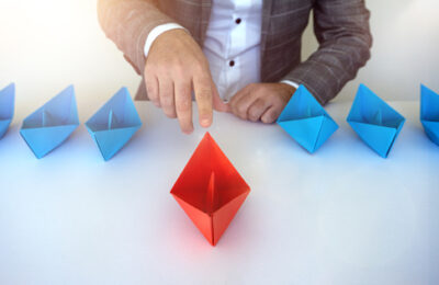 Businessman choosing red origami a leadership and business goal concept
